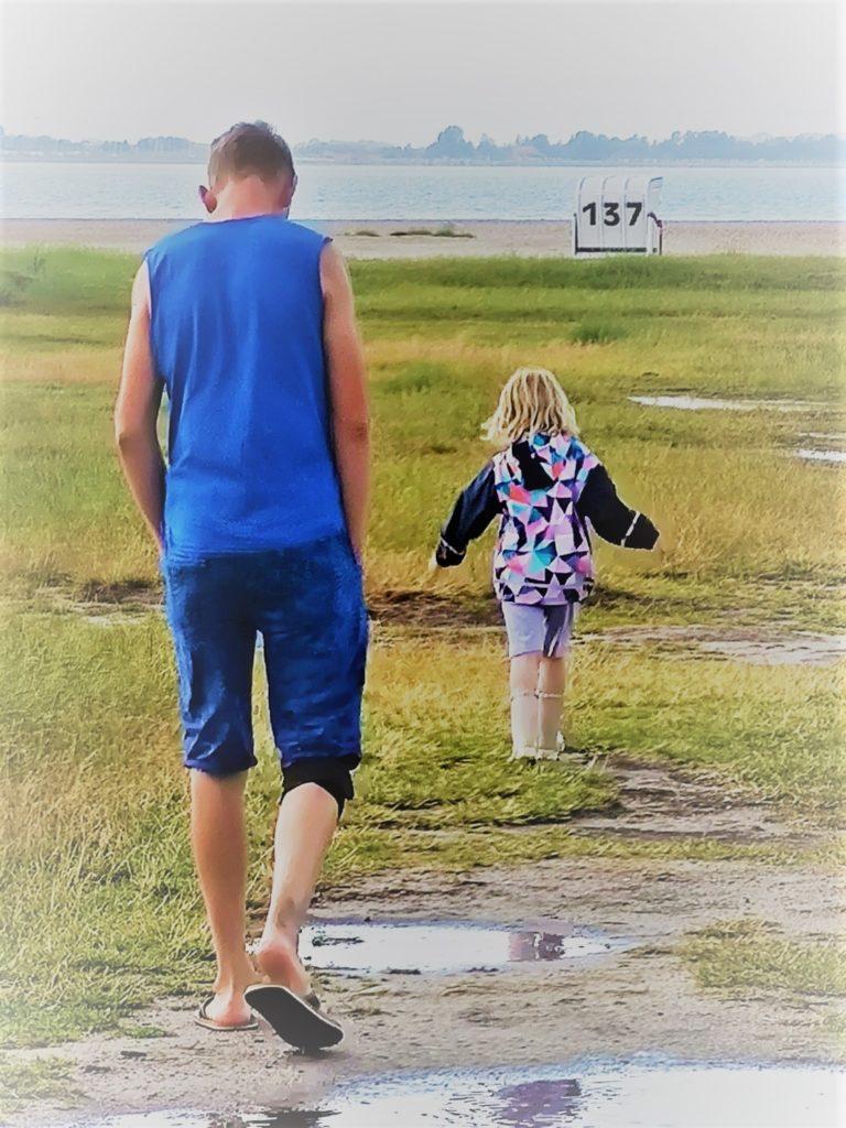 Bild: Vater und Kind. Das Kind läuft vor.